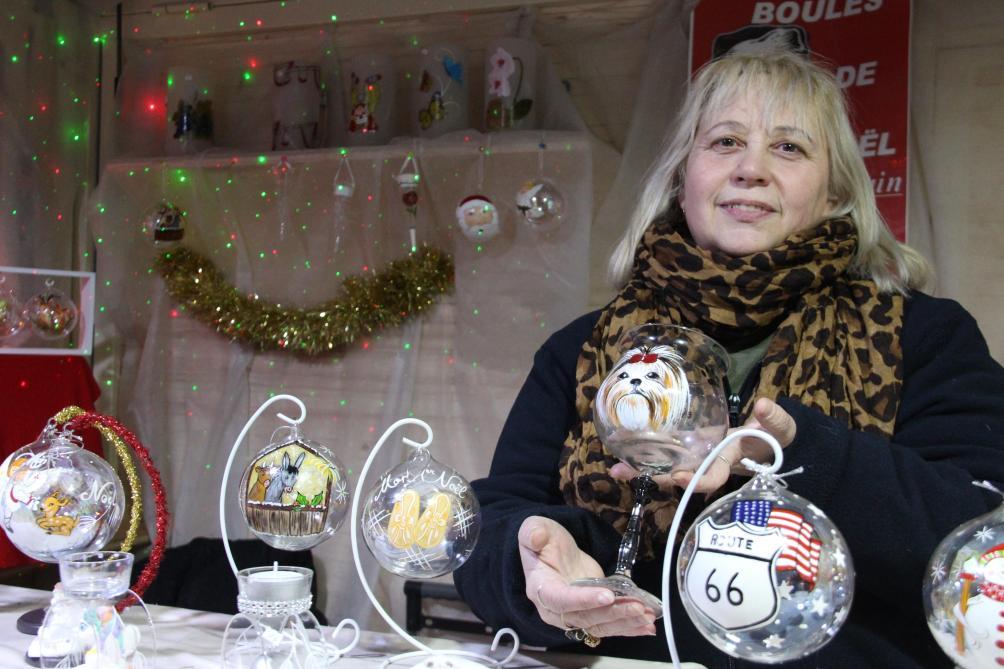 Elle peint sur des boules de Noël au marché de Châlons